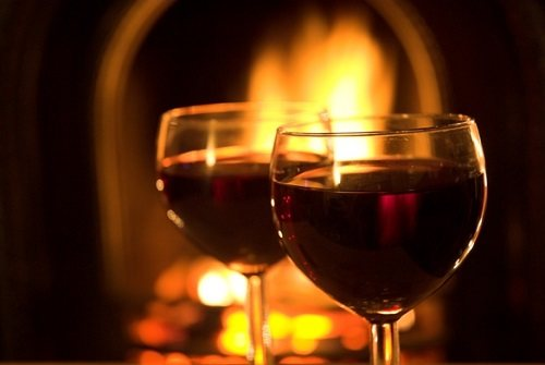 Enjoying red wine next to the cozy fireplace