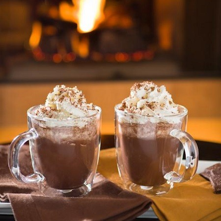 Two hot chocolates next to the cozy fireplace